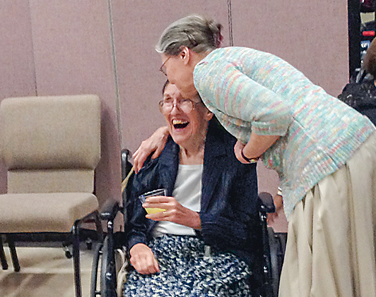 Sallie Satterthwaite (seated in wheelchair) receives a greeting from a friend at a reception in her honor Sept. 24, 2017, at Christ Our Shepherd Lutheran Church in Peachtree City. Photo/Cal Beverly.