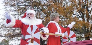 Santa and the Mrs. wave in last year's Fayetteville Christmas Parade. Staff photo.