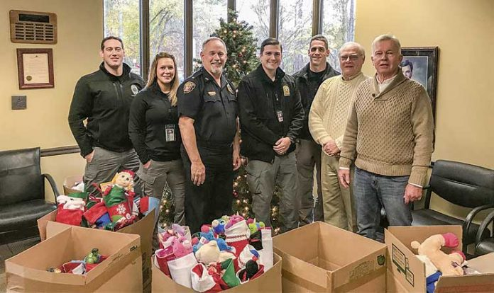 Carrying on a Peachtree City tradition of giving — Doing their part for the Peachtree City Police Department's annual Light Up the Night Toy Drive for needy kids are, from left, department staff Ryan MacCallum, Heather Scott, Stan Pye, Steven Stoyell and Gary Meier, joined by Beechwood subdivision residents Jerry Neese and Denny Spaulding, who have carried on the practice of supplying Christmas stocking for needy kids, an effort started in the early 1990s by the late David Hanahan. Photo/Peachtree City Police Department.