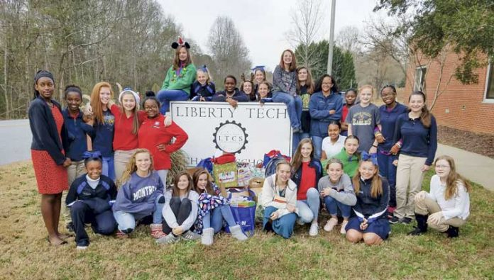 "Posing in front of the school sign are some of the numerous students at Liberty Tech Charter School in Brooks who formed an ""Ambassadors 4 Kids"" club to prevent bullying. Photo/Submitted."