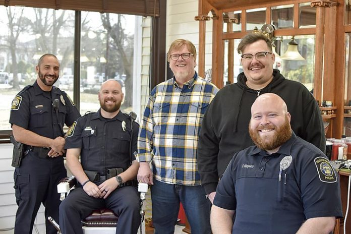 Awaiting their cuts are (L-R in uniform) Officer Eddie Hernandez, Officer Eric Tilley and Officer Tyler Simpson. Barber Sam Burch is standing left in the yellow checkered shirt beside barber Tyler Powell. Photo/Fayetteville PD.