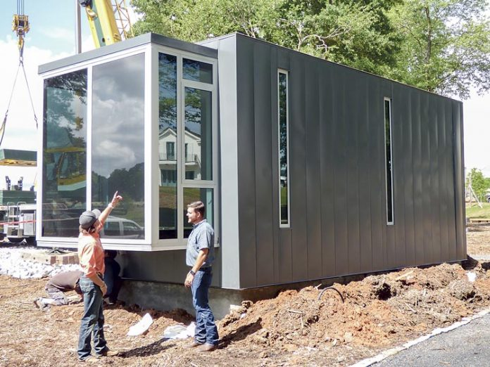 Kasita, Inc. representative Matt Hensley, left, and Pinewood Forest Builders Guild Director Brett Baker inspect the new Kasita micro-home delivered to Fayetteville on May 17. Photo/Ben Nelms.