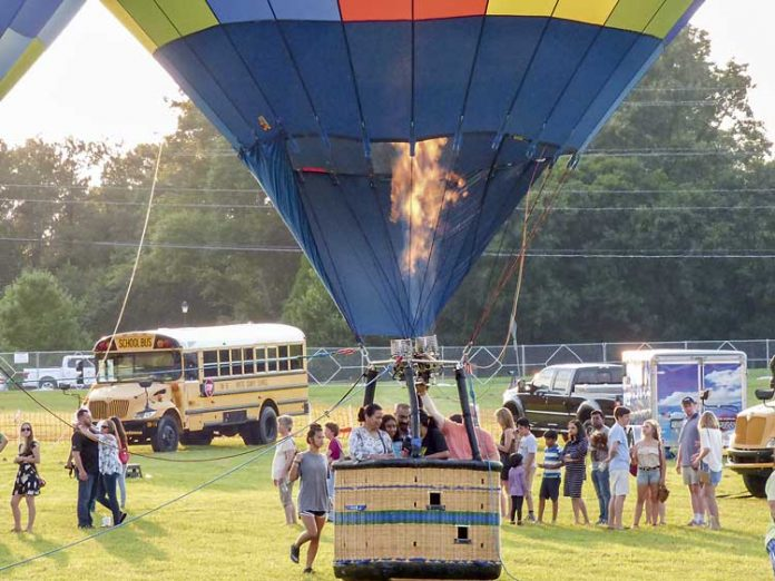 Firing up for high-flying fun — Passengers grab onto the basket rails in preparation for their hot-air balloon ascent Saturday south of Fayetteville as lines of riders await their turns. Thousands turned out for the annual county event. Photo/Ben Nelms.
