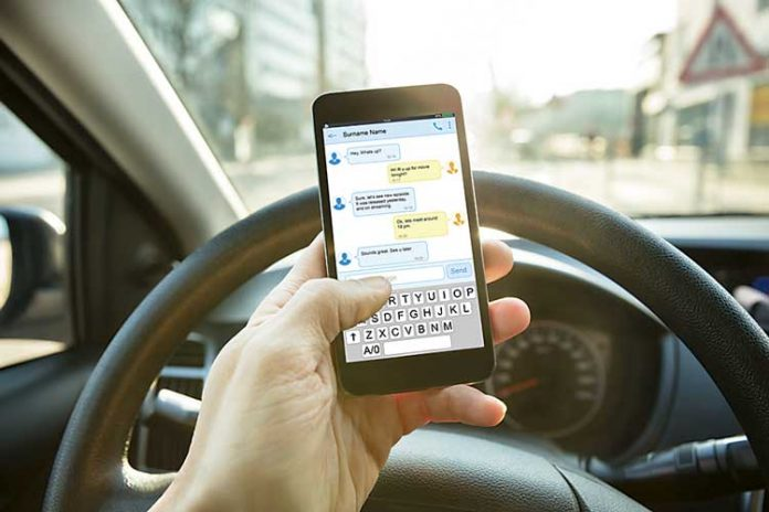 Man hold cellphone while driving. Photo/Shutterstock.
