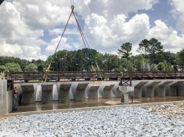 The last bridge span was positioned on the spillway for Lake Peachtree last week. The span still has to be filled with concrete, along with other assorted work. For perspective on the scale of the structure, yes, those tiny figures at the left on a lift and at center right beneath a piling are indeed grown men. Photo/Vanessa Fleisch.