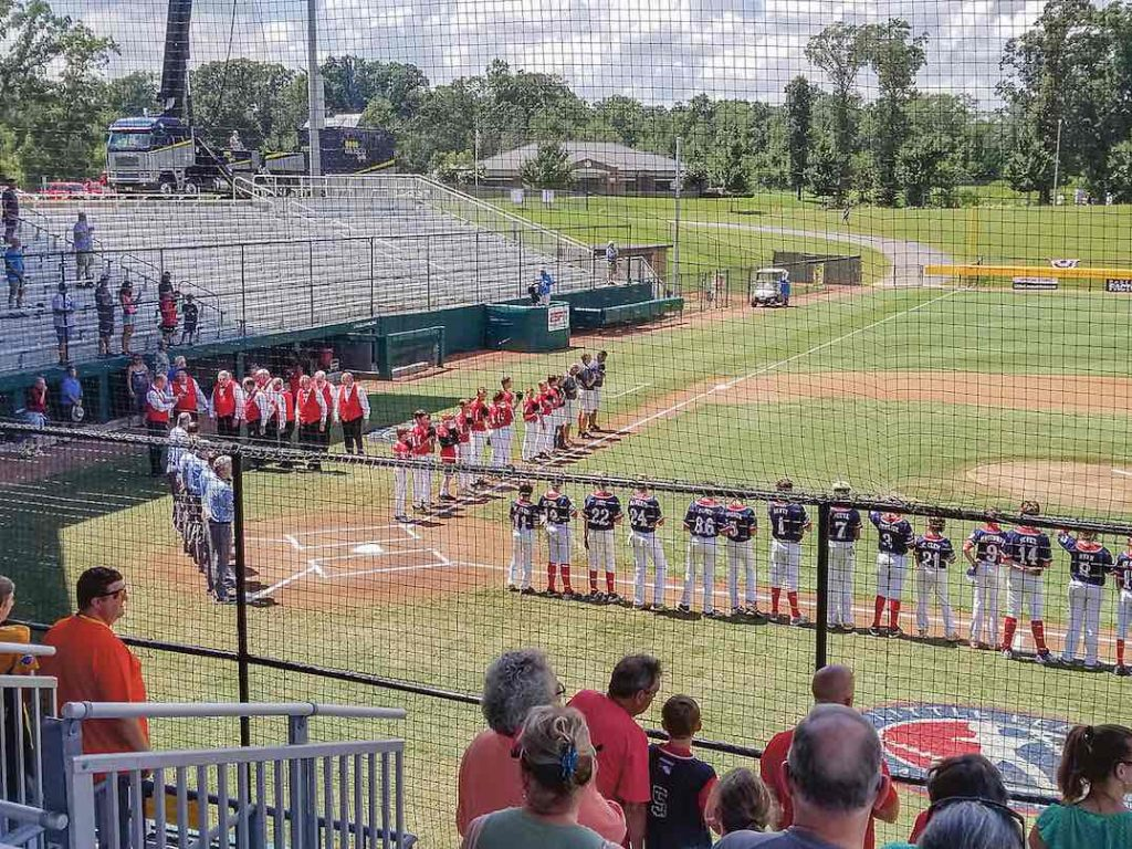 Little League players, coaches and fans stand for the National Anthem. Photo/Ken Miller.