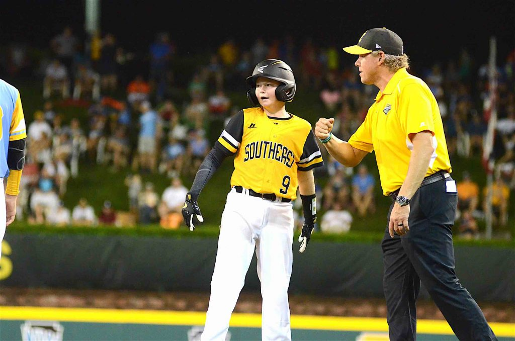 Peachtree City Little League's Chase Fralick talks with his coach after connecting with a single during the second day of the Little League World Series. Photo/Brett R. Crossley.