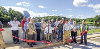 County staff and officials (including county commission Chairman Eric Maxwell cutting the ribbon and Commissioner Chuck Oddo nearby at left), project representatives and a group of neighbors attended the Aug. 30 ribbon cutting for the $3 million Emerald Lake Dam project funded by 2017 SPLOST (special purpose local options sales tax) dollars. The new dam and spillway southeast of Fayetteville was designed to meet Category 1 dam standards. Photo/Ben Nelms.