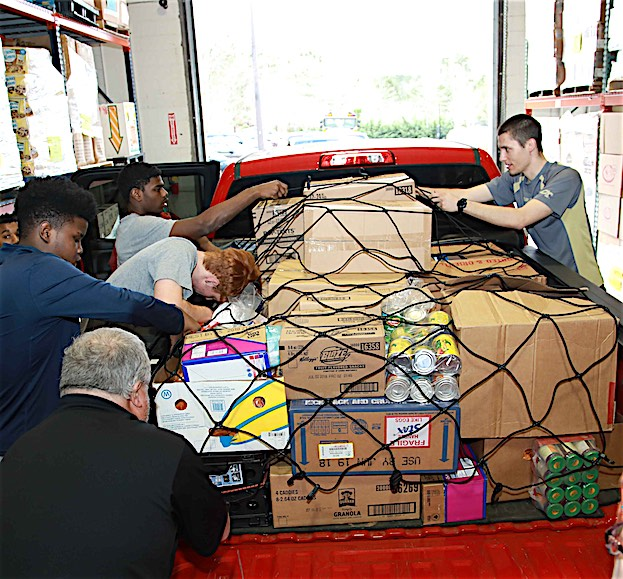 Volunteers secure a load of donated food. Photo/Midwest Food Bank.