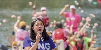 "Anna Seville sings ""You Lift Me Up"" at the edge of the Lake McIntosh pier Saturday afternoon during festivities for the annual Rotary Club Dragon Boat Races. Photo/Markus Schwab Photography."