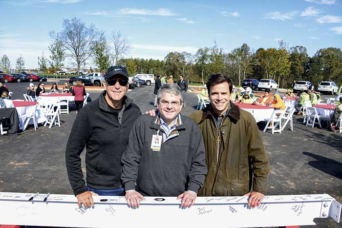 Pinewood Forest President Rob Parker, Piedmont Fayette CEO Michael Burnett, and Brasfield and Gorrie Vice President Reed Weigle with the final steel beam of the Piedmont Wellness Center at Pinewood Forest. Photo/Christopher Fairchild.