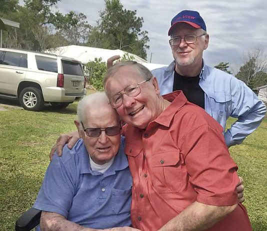Senoia resident Bob Lisle (in red shirt) gives his biological father, 88-year-old Floyd Sheffield, a hug as the two meet for the first time in March in Winterhaven, Fla. Standing nearby is Bob's brother, Jeff Sheffield. Photo/Submitted.