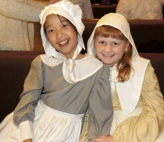 """Crossroads Christian School fifth-grade students Hannah Cooke and Katie Ferrell take a moment after their school's Thanksgiving play Nov. 15. Every student performed in """"The First Thanksgiving,"""" which commemorates the Pilgrims' quest for religious freedom, God's provision, and the friendship of Native Americans to the newcomers. Photo/Submitted."""
