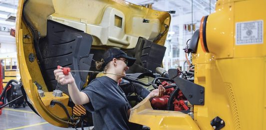 Lindsey Crook performs routine maintenance check on one of the school system's buses. Photo/Fayette County School System.