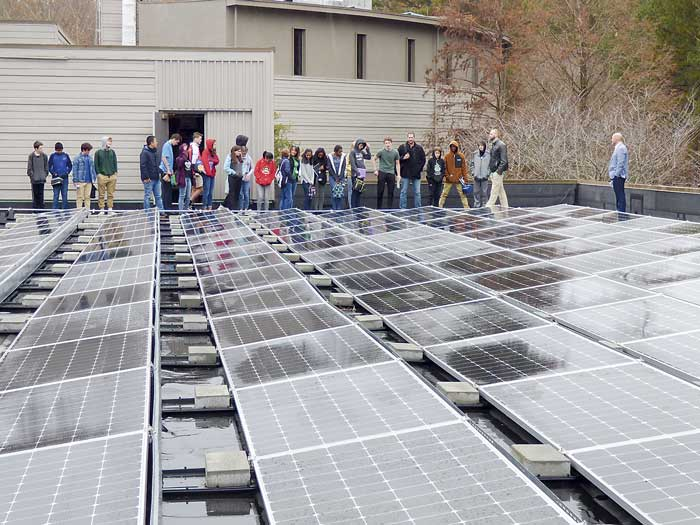 McIntosh High School students stand next to the massive rooftop power array. Photo/Ben Nelms.