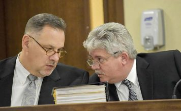 Peachtree City Manager Jon Rorie (R) confers with City Attorney Ted Meeker at a City Council meeting. Photo/Cal Beverly.