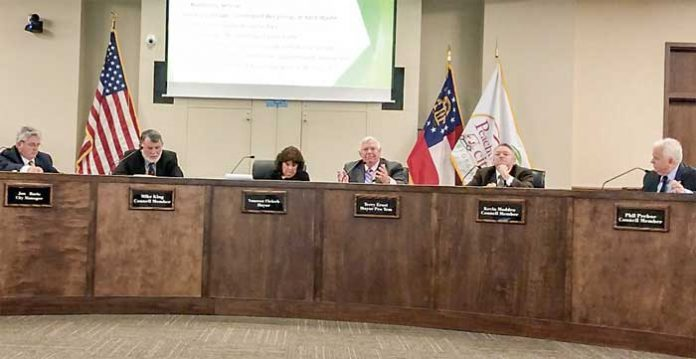 Members of the Peachtree City Council listen to Councilman Terry Ernst (3rd from right) explain his vote against a trash pickup proposal. Also shown are (L-R) City Manager Jon Rorie, Councilman Mike King, Mayor Vanessa Fleisch, Ernst, Councilman Kevin Madden and Councilman Phil Prebor. Photo/Cal Beverly.