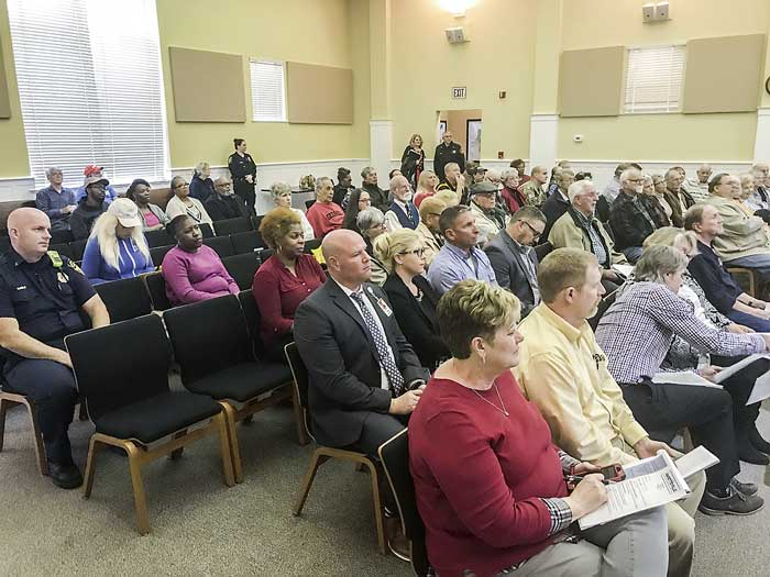 Below, a group of neighbors southeast of a helipad site approved March 7 by the Fayetteville City council spoke in opposition to a plan by Air Evac to establish a one-chopper, emergency medical transport site on Promenade Parkway in the Fayette Pavilion area. Photo/Ben Nelms.