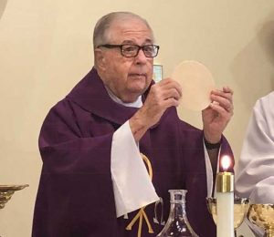 Father Paul Massey administering the Eucharist in 2019.