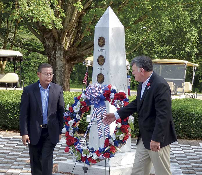 Peachtree City resident Anh Nguyen (L), a survivor of the Battle of Hue during the Vietnam War, and Peachtree City Councilman Mike King place a wreath at the Memorial Day ceremony held May 27 in Peachtree City. Photo/Ben Nelms.