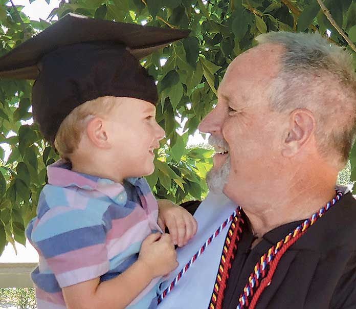 Two-and-a-half-year-old Kayden Pye celebrates with his grandfather, Assistant Police Chief Stan Pye, at Georgia Military College Commencement Ceremonies June 1. Photo/Submitted.