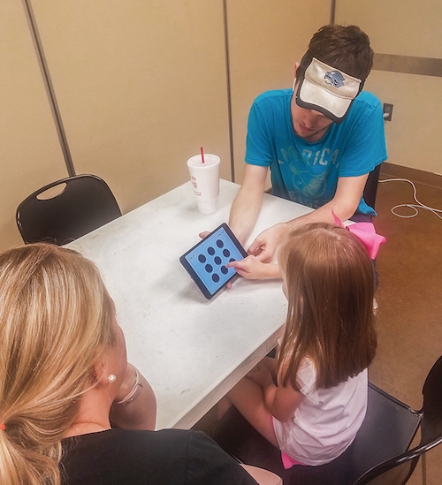 Below, Fayette County Community Youth Football member Nick Brown works with a youngster taking the concussion baseline test given to the organization's football players and cheerleaders. Photo/Submitted.