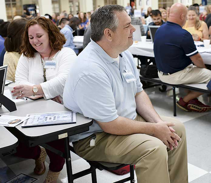 <b>McIntosh High School Teachers Janell Brown and Paul Sams enjoy a laugh as Dr. Barrow, Fayette County Public School System superintendent, shares a funny story during his welcome to the teachers. Photo/Fayette County School System. </b>