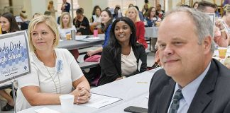 Sandy Creek High teacher Laura-Leigh Reynolds sits across from interim principal Richard Smith as they listen to Kim Herron, director of elementary education, deliver the first welcoming remarks to kick-off the 2019 New Teacher Induction. Photo/Fayette County School System.