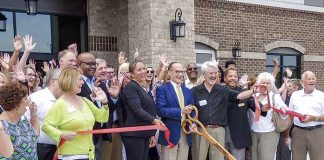 Among the large group at the June 27 grand opening for the HearthSide Club Lafayette active senior apartments in Fayetteville were, at center, Ga. Department. of Community Affairs Housing, Finance and Development Director Jill Cromartie, OneStreet Residential Senior Managing Partner David Dixon, project architect Bill Foley and Fayetteville Mayor Ed Johnson. Photo/Ben Nelms.