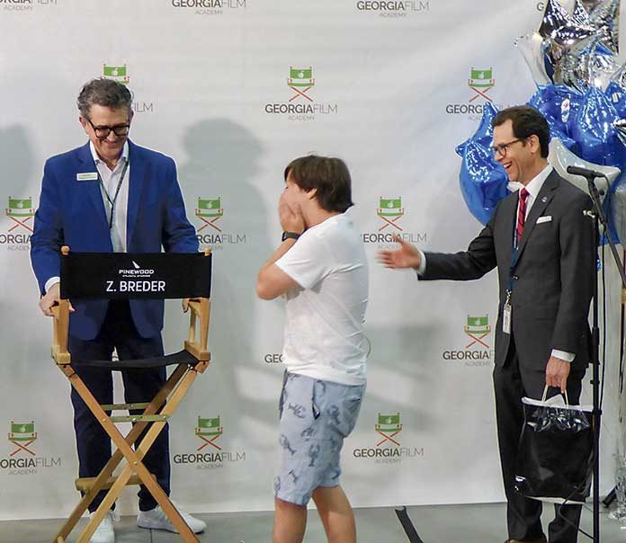 One of the many surprises for 14-year-old Zach Breder by way of Make-A-Wish Georgia, the Georgia Film Academy and Pinewood Atlanta Studios on July 9 was the presentation of Zach's director's chair. The chair will be put to good use when the academy and studio will assist Zach in writing and directing his own movie. Presenting the chair at the ceremony on Stage A was Pinewood Atlanta Studios President Frank Patterson (L), and Georgia Film Academy Executive Director Jeffrey Stepakoff. Photo/Ben Nelms.