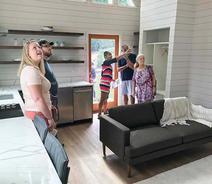 "Visitors at the 536 sq. ft. ""Peak"" micro home at Pinewood Forest on July 20 got a look at a sampling of the smart home technology with which all six homes in the development's first Micro Home Village are outfitted. Photo/Ben Nelms."