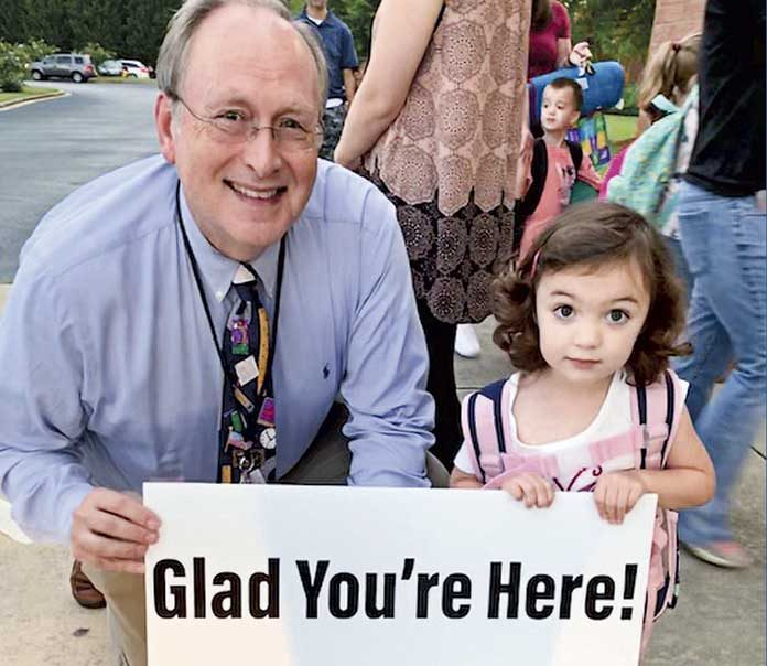 Fayette County Public School Superintendent Dr. Joseph Barrow holds a positive sign with Lillian, a preschooler at Cleveland Elementary. Photo/Fayette County School System.