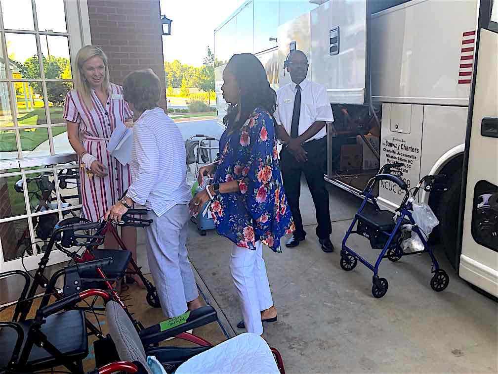 Logan Johnston (L), executive director of Heartis Fayetteville, welcomes residents and staff of Portside at Grande Dunes from South Carolina. Photo/Joyce Beverly.
