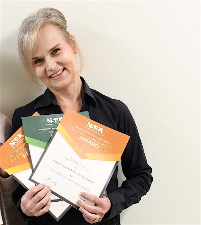 Melinda Berry-Dreisbach, public information officer, proudly displays the awards she received from the National School Public Relations Association.