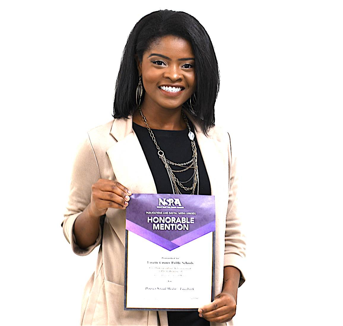 <b>Nia Washington, public information specialist, proudly displays her award for social media from the National School Public Relations Association. Photo/Fayette County School System.</b>