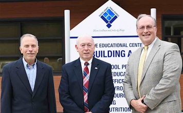 Former Fayette County Public School superintendents Dr. John DeCotis and Trigg Dalrymple take their place alongside current Fayette County Public School Superintendent Dr. Joseph Barrow in front of the school system's new logo. Photo/Fayette School System.