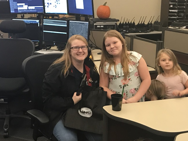 Fayette E-911 dispatcher Amber Heminger received an Oct. 14 visit from 9-year-old Delilah Austin, who called in a fire at her home on Oct. 11. Pictured, from left, are Heminger, Delilah and her sisters Isabella and Daniella. Photo/Ben Nelms.