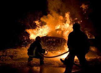 Shutterstock photo of firefighters at vehicle blaze.