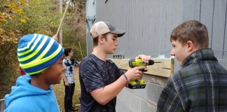 The Foundry High School students working at the home of Fayetteville Vietnam veteran MacArthur Starr as a way to honor him included, from left, Najeh Hanif, Jackson Mayer and Tanner Tatum; with Reese Wackes in the rear. Photo/Submitted.