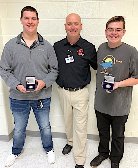 Scott Schmitt, public safety instructor at Whitewater High, presents students Patrick Lampl and Jason Kirkbride with the first challenge coins he will be awarding to students in his classes each month who demonstrate positive character traits and hard work inside and outside the classroom. The coins are funded by a grant he received from the Fayette County Education Foundation. Photo/Fayette County School System.
