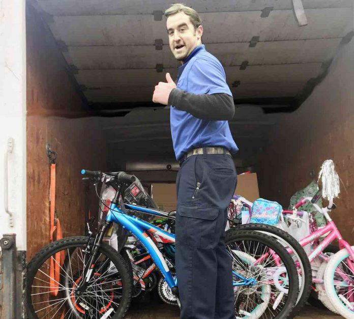 Warehouse employee Chase Callahan gives a big thumbs up as he loads bicycles inside his delivery truck. The bicycles are fulfilling the wishes of students included in this year's CARE Angel Project. Photo/Fayette County School System.