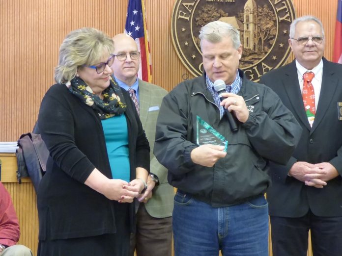 The retirement of longtime Fayette County Finance Department Director Mary Parrott was recently announced. Pictured with Parrot, at left, receiving an award for her service was County Administrator Steve Rapson. In the background were Commissioner Edge Gibbons and Chairman Randy Ognio. Photo/Ben Nelms.