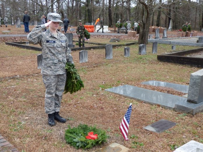 Civil Air Patrol Cadet and Peachtree City resident Skyla Ziegler salutes after placing a wreath at the gravesite of a veteran in the Fayetteville Cemetery at the Wreaths across America observance on Dec. 14. Photo/Ben Nelms.