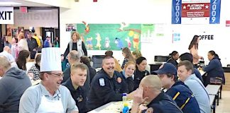 One of the chefs at the 29th Annual Pancake Breakfast held Jan. 25 at McIntosh High School took time to sit with firefighters enjoying a meal. As it turns out, the chef looks a lot like Peachtree City Fire Chief Joe O'Conor. Photo/Ben Nelms.