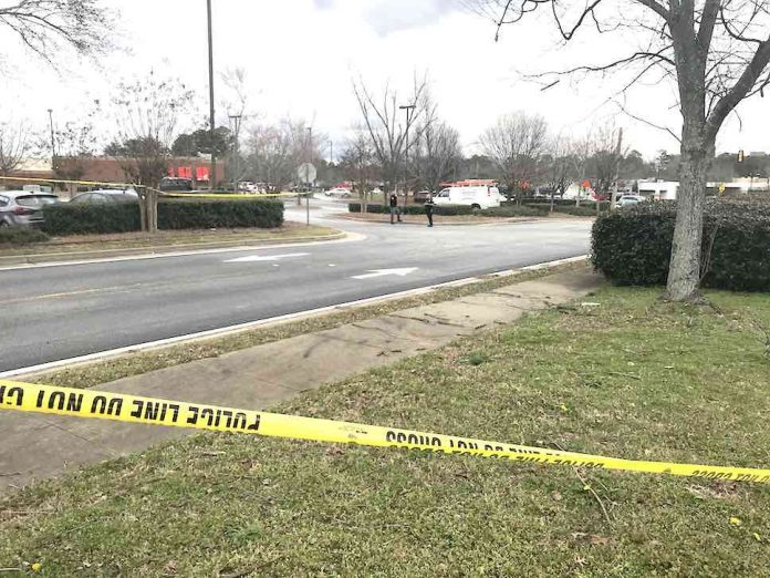 Fayetteville police are shown behind a police tape in a restaurant parking lot off Hwy. 85 jto the north of the shooting incident Monday. Photo/Ben Nelms.
