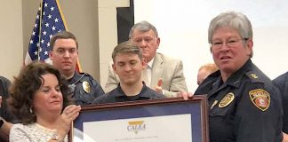 Backed by members of the Peachtree City Police Department, Mayor Vanessa Fleisch (L) and Chief Janet Moon display the award announcing the department's recent accreditation again by CALEA. Photo/Cal Beverly.