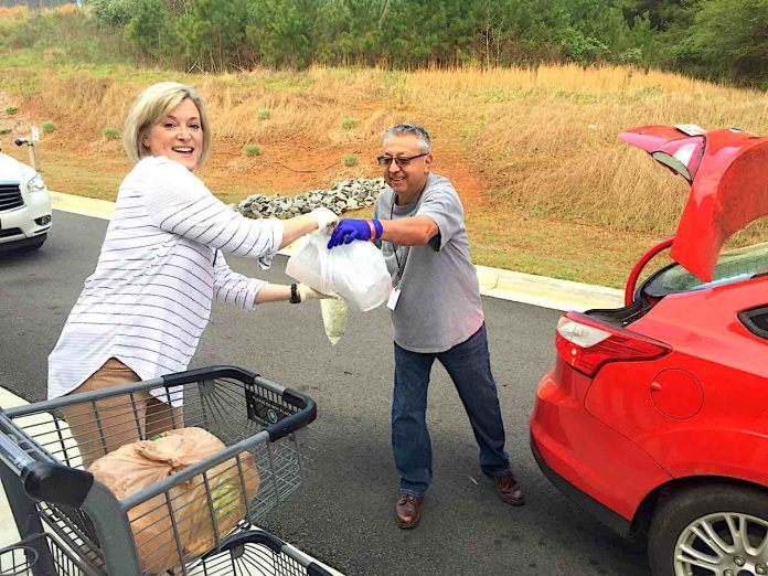 Real Life Centers volunteers Vicki Free and George Holguin assist with serving families with food at the Real Life Center, 975 Hwy 74 North, Tyrone on Thursday, March 19. Photo/Real Life Center.