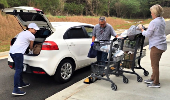 Real Life Center volunteers Vicki Free, George Holguin, and Jennifer Dobbs serve drive-thru clients.