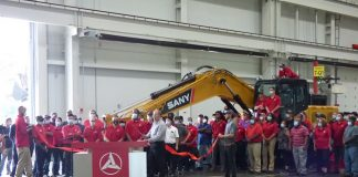 The manufacturing team at SANY America in Peachtree City was recognized June 24 for their efforts in completing the company's 100th SY215C excavator. The team is assembled in front of the large machine. Photo/Ben Nelms.