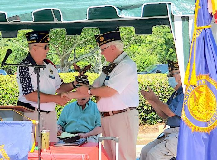 New Post 50 Commander Mark Gelhardt presents an eagle statue to the outgoing Commander Leigh Blood. Photo/Submitted.